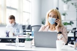 Return to work after covid-19 quarantine. Busy millennial woman in protective mask talking on phone and typing on laptop at workplace with antiseptic in modern office interior, free space