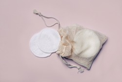 Reusable Bamboo Cotton Makeup Remover Pads in net bag on pink background. Zero-waste, sustainable lifestyle concept.