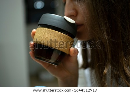 Reusable Coffee Eco Cup. Toughened Glass Cup & Natural Cork Band. Secure silicon lid. Friendly, Spill Proof Travel Mug with Lid | Black.A young girl drinks from a reusable cup. Keep Cup