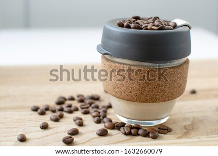 Reusable Coffee Eco Cup. Toughened Glass Cup & Natural Cork Band. Secure silicon lid. Reusable eco cup on a wooden background.Eco-Friendly, Spill Proof Travel Mug with Lid | Black. Keep Cup