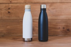 Reusable eco-friendly black and white stainless steel thermo bottles on wooden rustic background. Copy space. Zero waste, no plastic, sustainability. Bring your own water bottle concept.