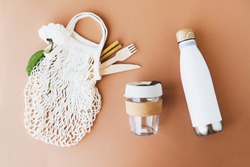 Reusable eco-friendly cotton mesh bag with bamboo drinking straws, wooden cutlery, glass cup and stainless steel thermo bottle on brown background. Copy space, top view. Zero waste summer picnic.