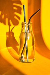 Reusable Metal Straws in glass bottle with water on yellow background with plant shadow - Stainless Steel, Eco-Friendly Drinking Straw Set. Zero waste. Plastic free. Stainless Steel Metal Straws.