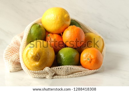 Reusable produce bag filled with fresh citrus fruits. Zero waste concept. Copy space. #1288418308