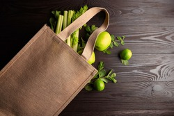 Reusable shopping bag with fresh fruits and greens on wooden background, top view. Jute bag (eco-friendly material), green apples, limes, celery on brown table. Healthy food, useful organic products