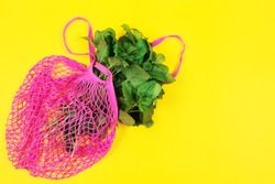 Reusable shopping bag with greens on yellow background. Mesh cotton bag. Zero waste, plastic free concept. Top view
