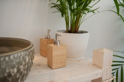 reusable wooden eco-friendly wooden bottles for liquid soap and shampoo with silver spouts on a wooden tabletop and tropical plant on the background