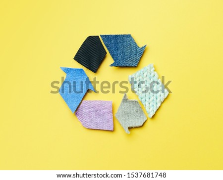 Reuse, reduce, recycle concept background. Recycle symbol made from old clothing on yellow background. Top view or flat lay.