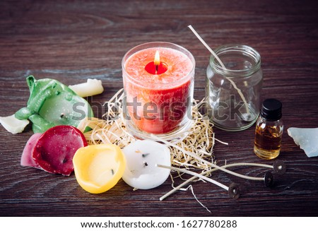 Reusing old candles leftovers and making melting a new one: various ingredients on table: candle wicks, glass jar, old candles wax, aroma oil. New candle in glass in center.