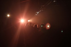 Revellers at a warehouse party captured in silhouette