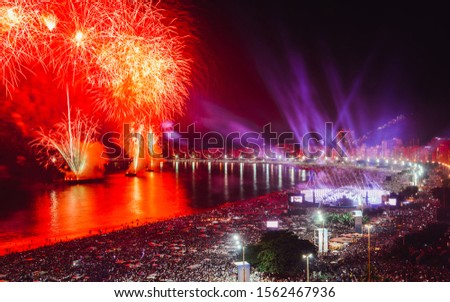 Revellers, both locals and tourist, enjoy the breath-taking New Years fireworks display along Copacabana Beach, Rio de Janeiro, Brazil. The largest party in the world. Long exposure deliberate blur