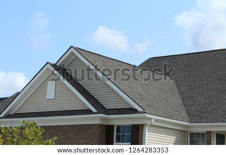Reverse double gable close up on residential home. Roof line of traditional home with one gable running one way and reverse gables running the other.  Deep overhangs on gables.