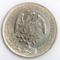 reverse of a Mexican 8 reales coin with the country's coat of arms with an eagle holding a snake with its beak on a cactus, surrounded by an oak and olive branch on a white background.