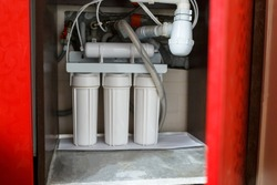 Reverse osmosis water purification system in red closet at home. Installation of water purification filters under kitchen sink in red cupboard. Clear water concept