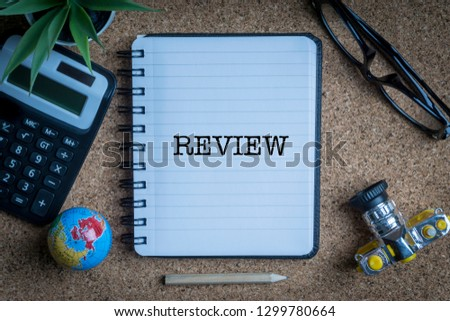 REVIEW inscription written on book with globe,eyeglasses, calculator, camera, pencil and vase on wooden background with selective focus and crop fragment. Business and education concept Stock fotó ©