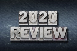 review 2020 phrase made from metallic letterpress on dark jeans background