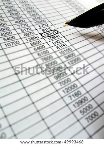 reviewing the financial data spreadsheet with black ink pen. budget analysis concept
