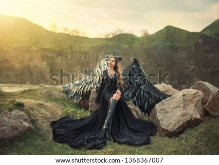 Stock Photo revived gargoyle, queen of night watching sunrise, girl in long light black dress with black feather wings sits on rocks with open leg in high boots, mysterious mythical creature, creative art photo