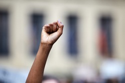 Revolutionary fist up in the air above head of a dark skin young person at a rally or protest out in a city downtown