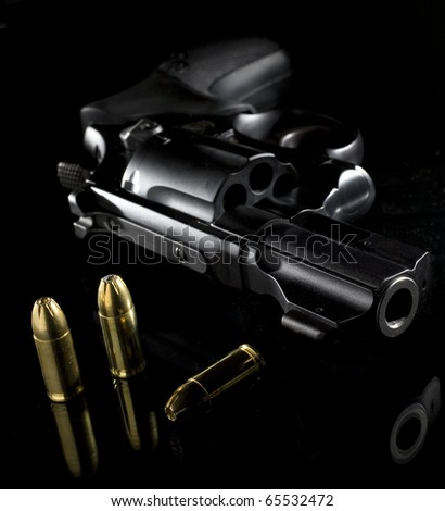 revolver and some cartridges on a black piece of glass
