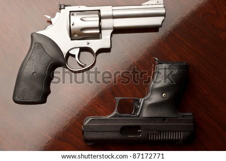 Revolver on surface with 9 mm handgun