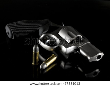 Revolver that is on a glass nightstand with very low light