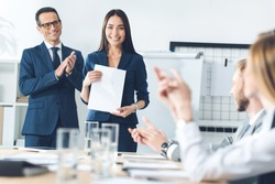 rewarded happy manageress holding blank paper while colleagues clapping to her