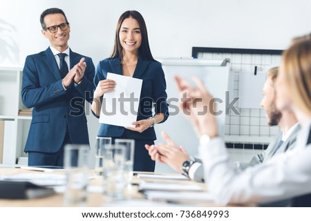 rewarded happy manageress holding blank paper while colleagues clapping to her #736849993