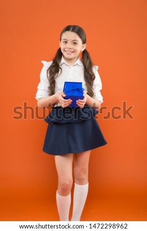 Rewarding for efforts. Girl opening gift. Tidy adorable pupil open gift box. Educational program for gifted kids. Happy birthday. Knowledge day. Schoolgirl surprise gift. Holiday celebration.