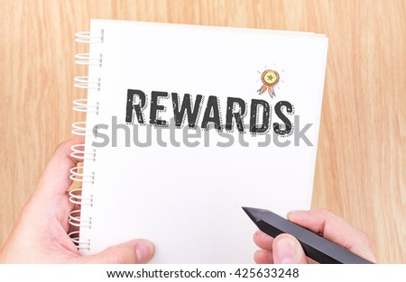 Rewards word on white ring binder notebook with hand holding pencil on wood table,Business concept. #425633248