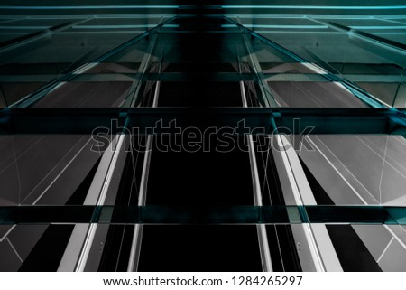 Reworked close-up photo of office building exterior fragments. Glass wall or ceiling with steel framework. Structural glazing. Abstract modern architecture image in teal and gray colors.