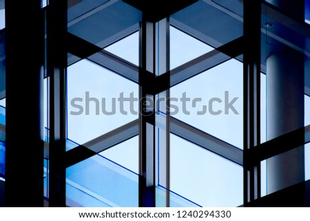 Reworked close-up photo of office building fragment in shadows against clear blue sky. Glass wall with metal framework. Structural glazing. Abstract modern architecture background. #1240294330