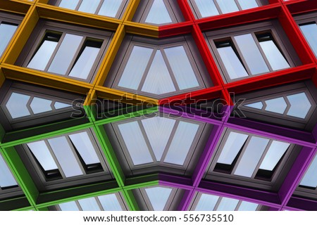 Reworked photo of ajar windows with multicolor frames reflecting blue sky. Optimistic abstract image on the subject of modern residential or office architecture.