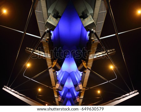 Reworked photo of cable-stayed bridge / suspension bridge illuminated in darkness. Modern urban architecture with electric lighting. Contrast night photo of luminous hi-tech cityscape #649630579