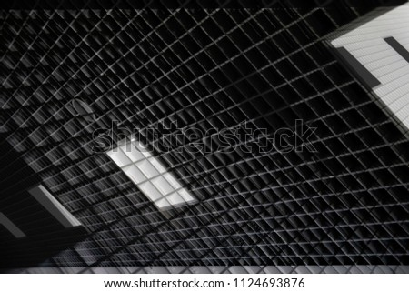 Reworked photo of dropped ceiling with grid structure resembling pitched roof with mansard windows. Abstract architecture background featuring modern office building interior.
