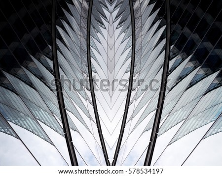 Reworked photo of hi-tech building fragment with reflections. Modern glass architecture combining curvilinear and angular shapes. Abstract industry or technology background.