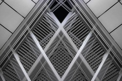 Reworked photo of industrial or office building interior fragment with backlit louvered ceiling and matte semi-transparent wall panels. Abstract black and white modern architecture image.