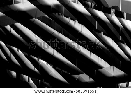 Reworked photo of office building fragment. Abstract modern architecture image resembling underside view of girders. Industry or technology motif. #583391551