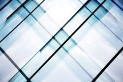 Reworked tilt photo of glass walls of office building. Abstract modern architecture background with geometric structure.