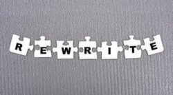 REWRITE - word composed of paper white puzzles on a gray background. Business concept