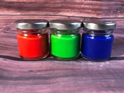 RGB Paint In Jars On Wood Background; Red,Green and Blue Acrylic Water Paints In Jars With Lids Close Up