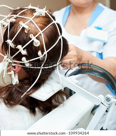 rheoencephalography - a doctor attaches electrodes on a patients head