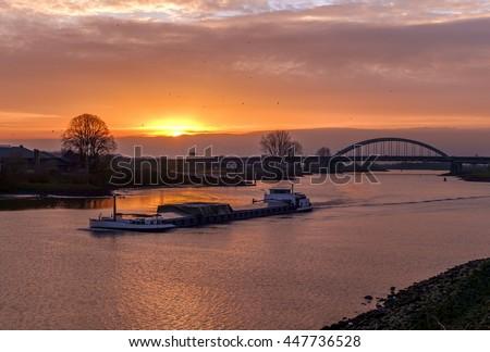 Rhine barge sailing on the river near a bridge at sunset