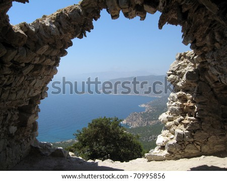 Rhodes island coast through wall opening of Monolithos castle ruins. Greece.
