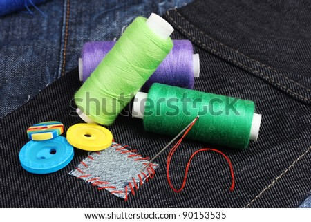 Rhomb-shaped patch on jeans with threads and buttons closeup