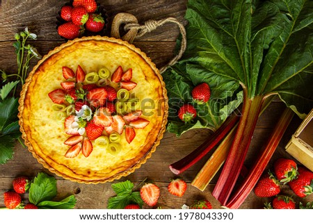 rhubarb cake, cheesecake on a wooden background, sweet dessert, summer, baked cake, sweet, delicious, rhubarb leaves, pie, berries, pieces of strawberry, dessert, classic strawberry cake