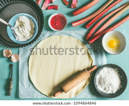 Rhubarb cake preparation. Kitchen table with pie dough, rolling pin, flour, egg and fresh red rhubarb stalks, top view. Seasonal cooking and baking concept