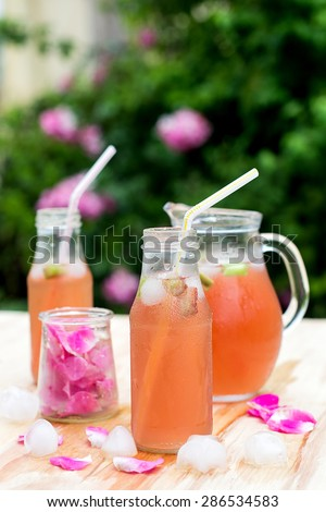Rhubarb hibiscus drink iced tea with rose petals in the garden. Selective focus