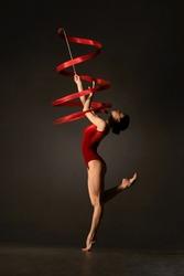 Rhythmic gymnast in red leotard with ribbon