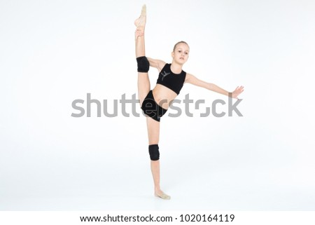 Rhythmic gymnastics caucasian blonde girl in black suite performing athelete exercises showing flexibility and acrobat balance on white background isolated
